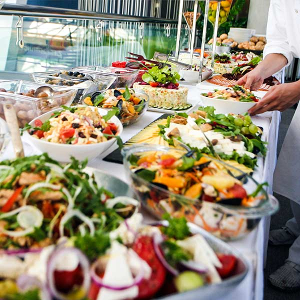 corporate catering buffet table with salads, and other trimmings with server setting up