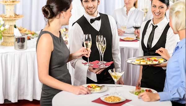 servers offering two women champagne and hors 'd'ouvres in social catering situation