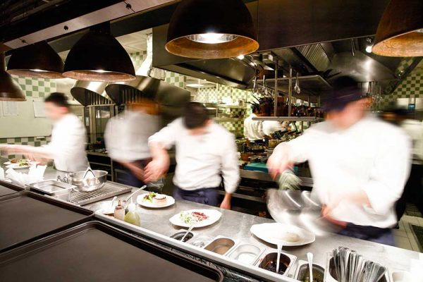 Busy kitchen with chefs preparing catered food