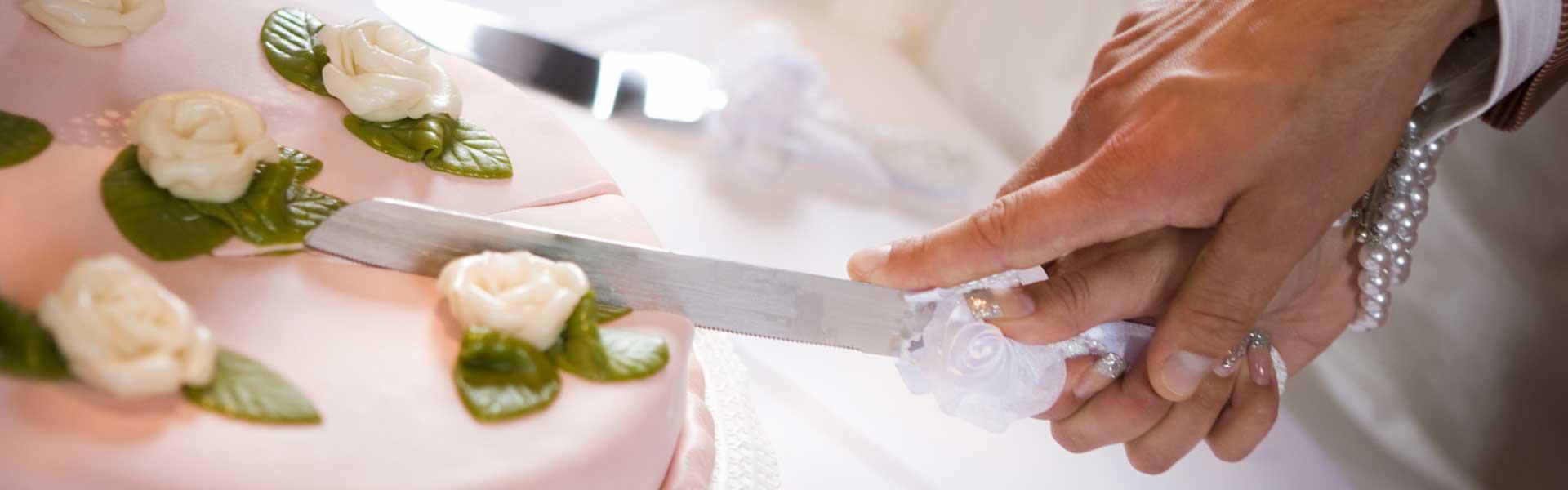 Couple slicing wedding cake