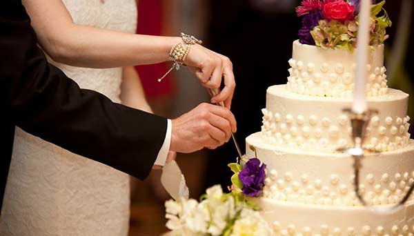 Couple cutting beautiful wedding cake with purple and white flowers