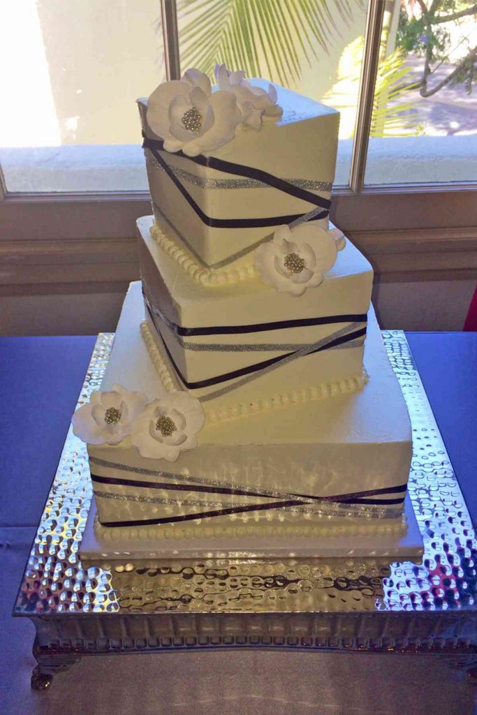 Simple wedding cake - offset square layers with angled silver and bronze ribbons and white flowers.