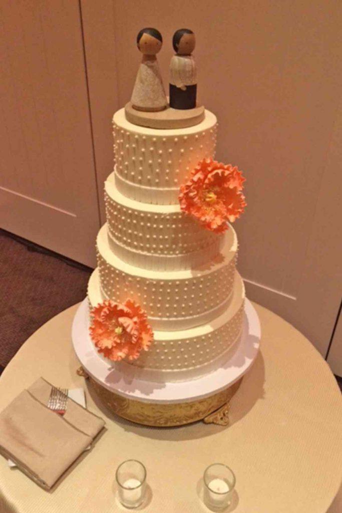 Simple wedding cake with raised polka dots amd orange flowers