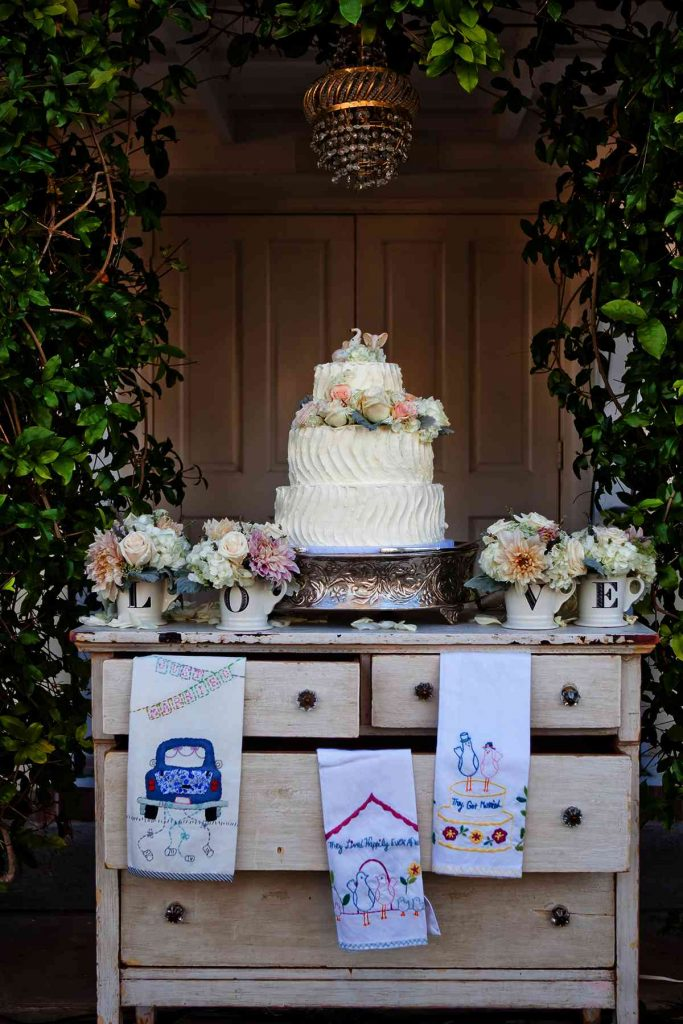 simple rustic-style wedding cake with vertical. wave-like contours. Decorated with peach and white flowers.