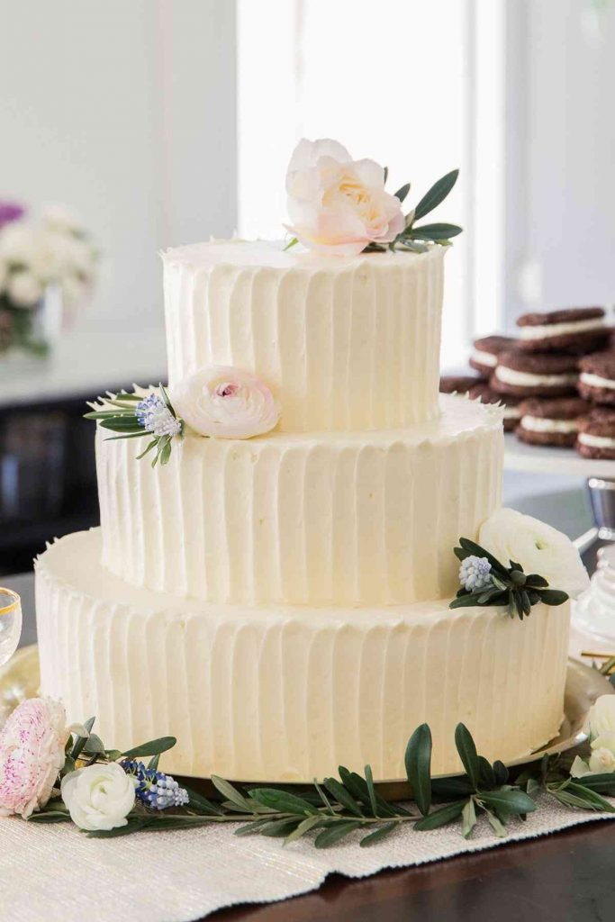 Simple wedding cake with vertical contours and pink magnolias